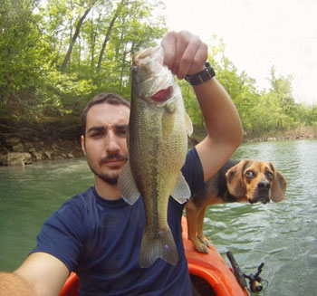 fishing dog photobomb man and fish